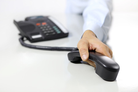 hand phone: hand with office phone on desk