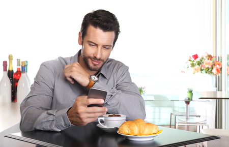 looking at watch: coffee break, handsome man use the smart phone at the bar with cappucino and croissant on the table Stock Photo