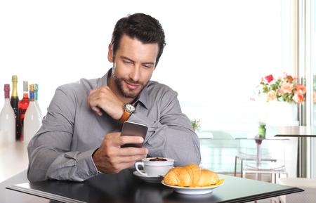 Koffiepauze, knappe man gebruik maken van de slimme telefoon op de bar met cappuccino en een croissant op tafel Stockfoto - 43694136