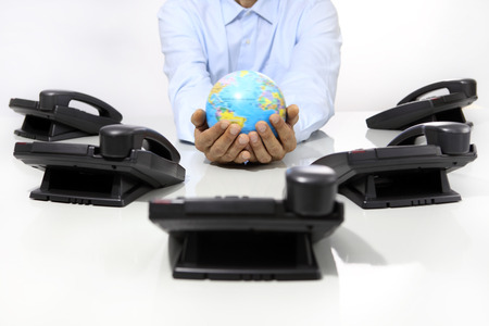 foreign country: hands globe with office phones on desk, global international support concept Stock Photo