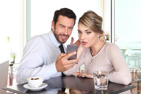 verrast gelukkige paar kijken de smartphone aan de bar