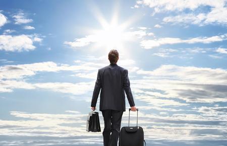 persona caminando: hombre de negocios de viaje con carro caminando hacia el cielo Foto de archivo