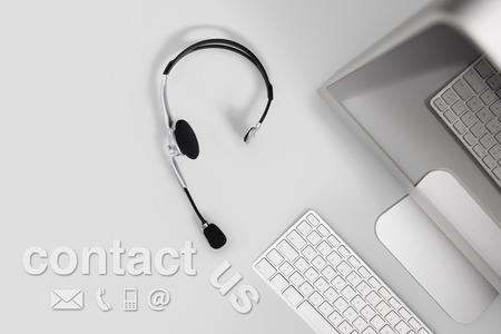 recepcionista: concepto contacto, vista superior escritorio con un audífono, equipo y póngase en contacto con nosotros de texto