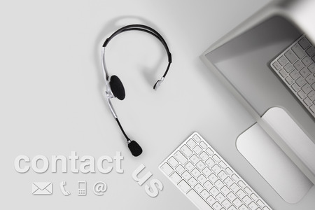 head icon: contact concept , top view desk with headset, computer and contact us text Stock Photo