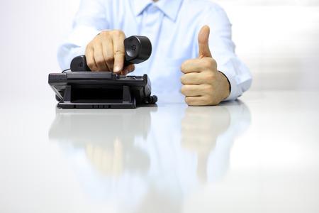 hablando por telefono: mano como con el teléfono de la oficina en el escritorio