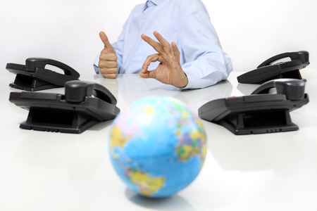 communications: globe and like hand with office phones on desk, global international support concept Stock Photo