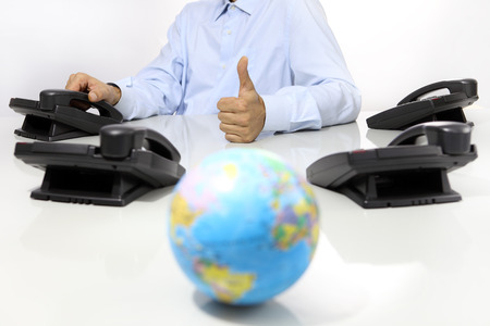 globe and like hand with office phones on desk, global international support concept Stock Photo