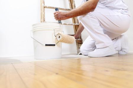 peintre en b�timent: peintre homme au travail avec un rouleau, un seau et d'�chelle, vue d'en bas