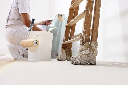 constructor: hombre pintor en el trabajo con un rodillo, cubo y la escala, vista desde abajo