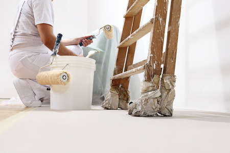 wall paintings: painter man at work with a roller, bucket and scale, bottom view