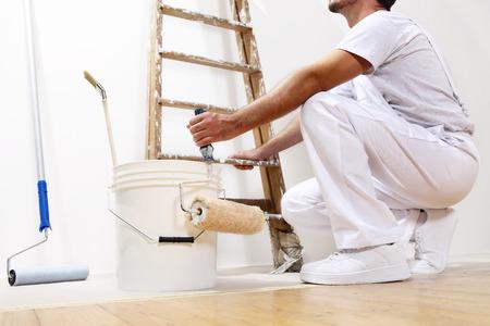 pintor: hombre pintor en el trabajo con un rodillo, cubo y la escala, vista desde abajo