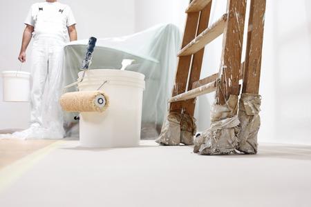 peintre homme au travail avec un rouleau, un seau et d'échelle, vue d'en bas