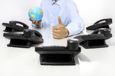 helpline: globe and like hand with office phones on desk, global international support concept Stock Photo