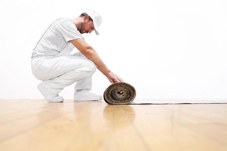 pintor: hombre pintor en el trabajo, tira el cartón en el suelo