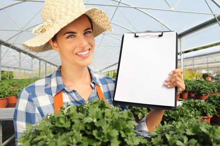 smiling woman in a greenhouse: smiling woman working in greenhouse, shows the blank clipboard