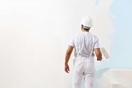 painting and decorating: painter man at work with a paint roller, wall painting concept