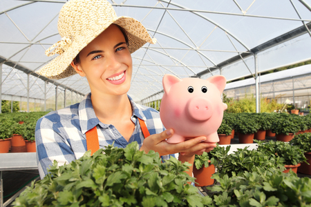smiling woman in a greenhouse: smiling woman in greenhouse, with piggy bank,
