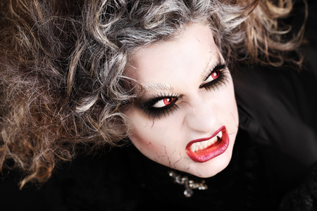 canines: vampire woman portrait with mouth open showing teeth canines, halloween make up