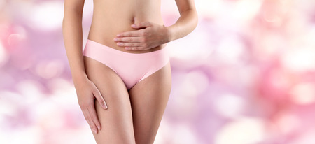 underwear girl: woman hands on belly, on pink background