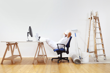 weekend: painter man after work rests with feet on the desk, weekend concept Stock Photo
