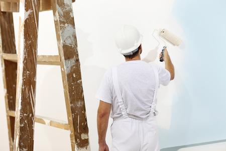 Schilder man aan het werk met een verfroller, muurschildering begrip Stockfoto - 47271040