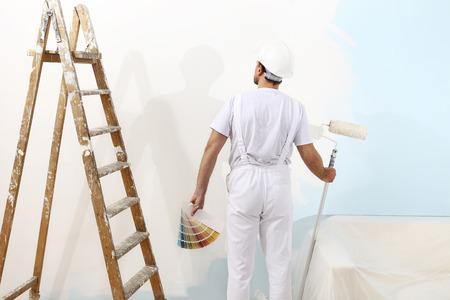 HOMBRE PINTANDO: hombre pintor en el trabajo con un rodillo de pintura y muestras de color, el concepto de pintura mural