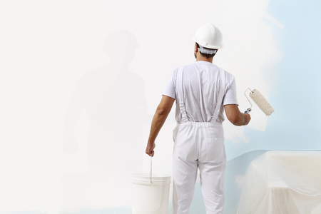 painting and decorating: painter man at work with a paint roller and bucket, wall painting concept