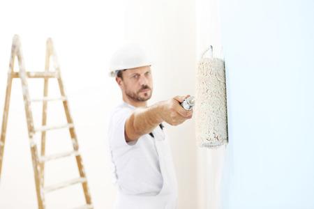 pintor de casas: hombre pintor en el trabajo con un rodillo de pintura, el concepto de pintura mural Foto de archivo