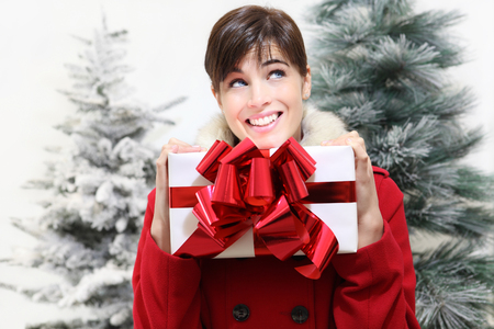 white coats: smiling woman with Christmas gift, looks up, with trees in the background Stock Photo