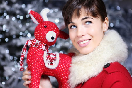 christmas woman: Christmas woman smiling with reindeer toy and look up