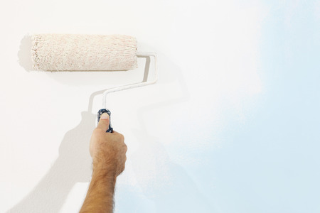 wall paintings: hand painter man at work with a paint roller, wall painting concept Stock Photo