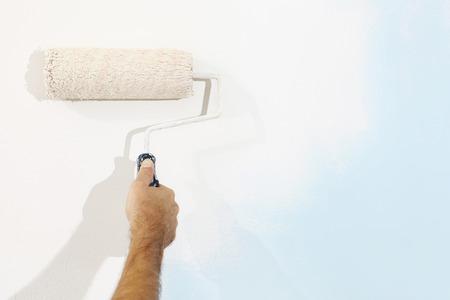 peinture: l'homme de main de peintre au travail avec un rouleau à peinture, le concept de peinture murale