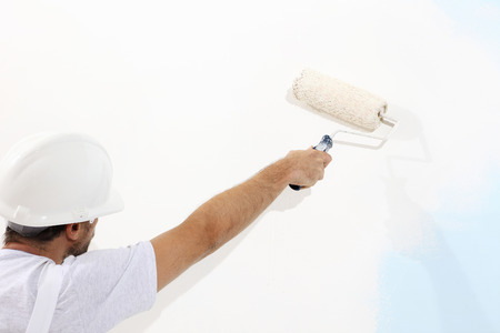 painter: painter man at work with a paint roller, wall painting concept