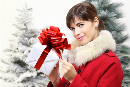 hand holding: woman with Christmas gift box, looks ahead, with trees in the background Stock Photo