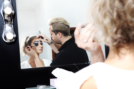 makeup artist applying mascara on eye lashes of model