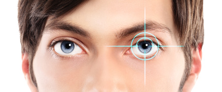 identification: Closeup of blue eyes from a young man and laser hologram on her eyes Stock Photo