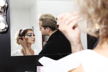 blushing: makeup artist with powder brush, blushing face of model
