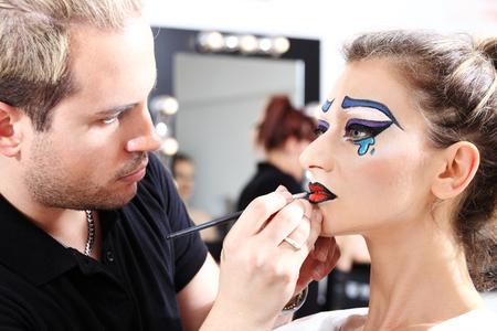 artist model: makeup artist applying lipstick on model lips with brush