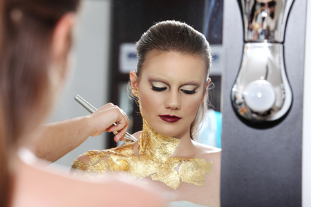 gilded: make up model at mirror, gilded body paint