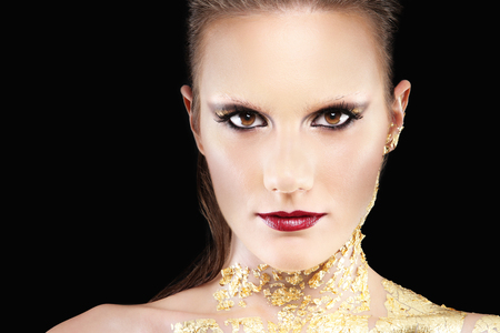 ojos negros: retrato de glamour maquillaje modelo, pintura corporal dorada Foto de archivo