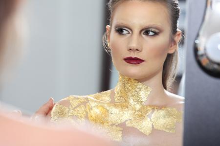 body paint: compensar modelo en el espejo, pintura corporal dorada Foto de archivo