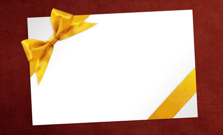 solemnity: cards with gift golden ribbon bow Isolated on red background