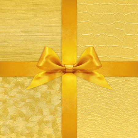 beautiful background: Shiny golden satin ribbon bow on gold background