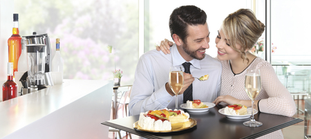 felicity: happy couple at the bar with champagne and fruit cake, love concept Stock Photo