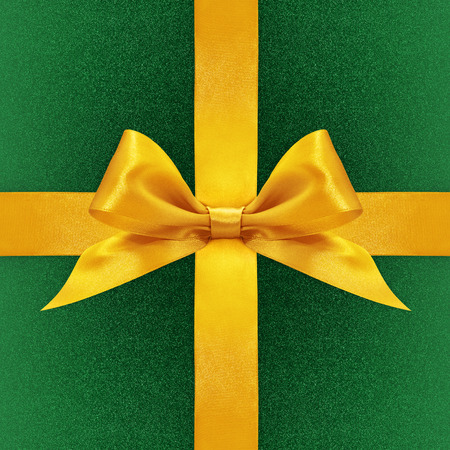 fabric texture: Shiny golden satin ribbon bow on green background