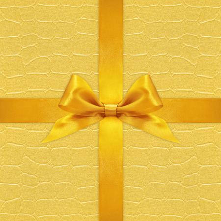 gold gift box: Shiny golden satin ribbon bow on gold background