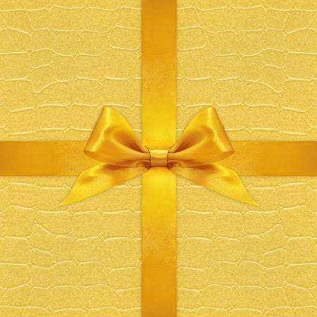 pattern background: Shiny golden satin ribbon bow on gold background