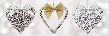 woven: Wooden Hearts braided with ribbon bow isolated on silver blurred light background Stock Photo