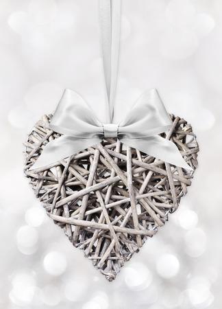 feier: Wooden Heart geflochten mit Bogen Band auf Silber isoliert verschwommen hellen Hintergrund Lizenzfreie Bilder