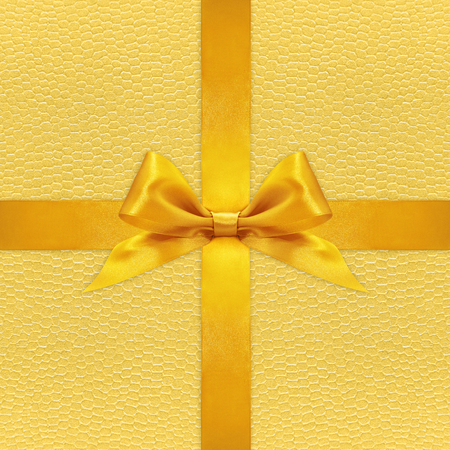 yellow paper: Shiny golden satin ribbon bow on gold background